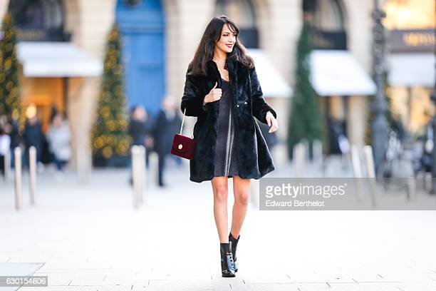 Sarah Benziane fashion and life style blogger wears a New Look full outfit consisting of black shiny boots a red bag a black faux fur coat and a gray...