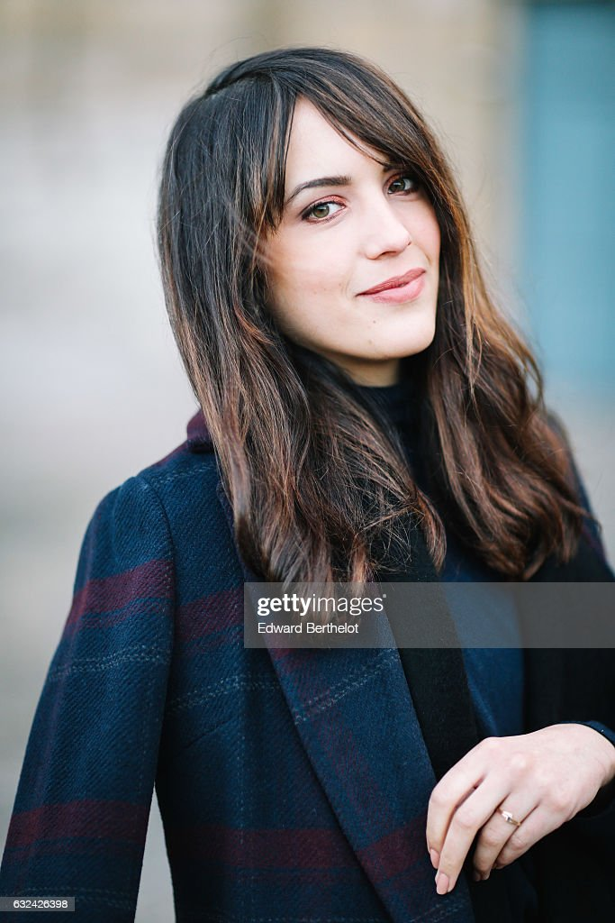 Sarah Benziane, fashion blogger from the blog Les Colonnes de Sarah, is wearing a Newlook long coat, Newlook blue denim jeans, Zara black shoes, and a Valentino Rockstud blue bag, during Paris Fashion Week Menswear Fall/Winter 2017/2018, on January 22, 2017 in Paris, France.