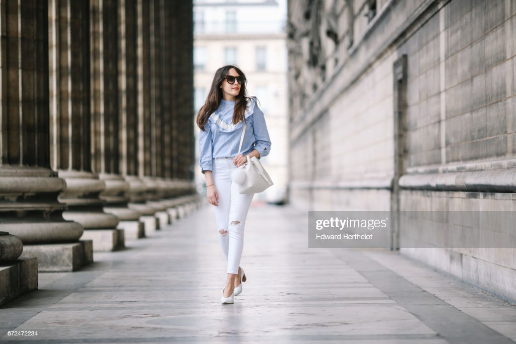 Sarah Benziane, fashion blogger Les Colonnes de Sarah, wears an Aliexpress blue ruffled top, Newlook white ripped denim jeans, a Lancaster white bag with a pompom, and Zara white shoes, on April 23, 2017 in Paris, France.