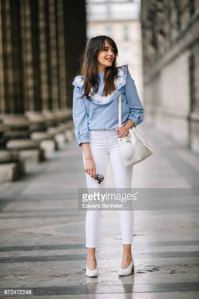Sarah Benziane fashion blogger Les Colonnes de Sarah wears an Aliexpress blue ruffled top Newlook white ripped denim jeans a Lancaster white bag with...