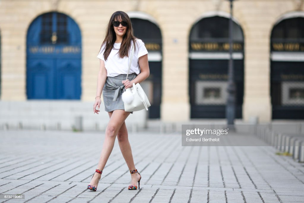 Sarah Benziane, fashion blogger Les Colonnes de Sarah, wears an H&M white t-shirt, a Newlook gray skirt with a knot, a Lancaster white bag with a pompom, and Mango flower print shoes, on April 23, 2017 in Paris, France.