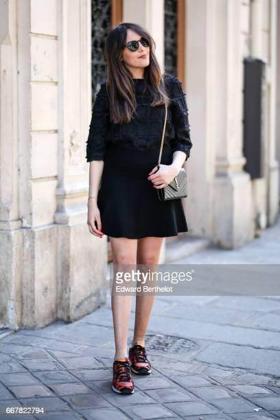 Sarah Benziane fashion blogger Les Colonnes de Sarah wears an HM black top a Cache Cache black skirt Saucony sneakers and a Saint Laurent YSL bag on...