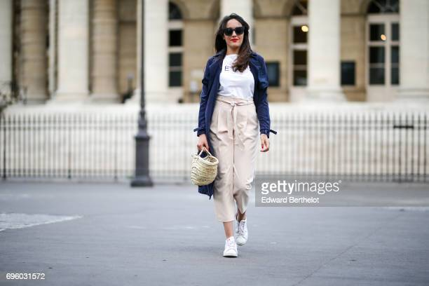 Sarah Benziane fashion blogger wears a New Look blue trench coat a white tshirt with the inscription CELFIE New Look cropped pants a straw basket...