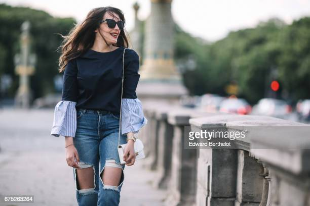Sarah Benziane fashion blogger wears a Ted Baker top Pimkie blue denim ripped jeans Newlook gold heels shoes a Furla white bag and Asos sunglasses at...