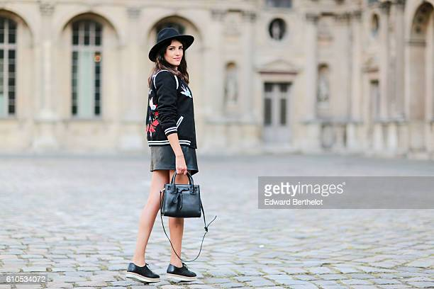 Sarah Benziane is wearing a black hat a New Look black bombers jacket with colored features and the word L'Amour written a Bershka pink top a Zara...