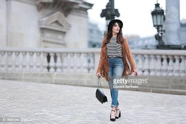 Sarah Benziane is wearing a JustFab fringe faux suede cognac colored jacket a Zara striped top vintage blue jeans Mango black shoes and a Mango black...