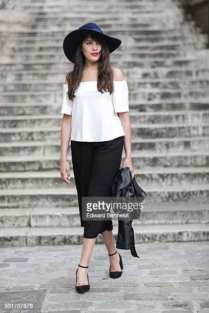 Sarah Benziane is wearing a New Look white top New Look black pants a Zara blue hat and Mango black shoes during a street style session on May 16...
