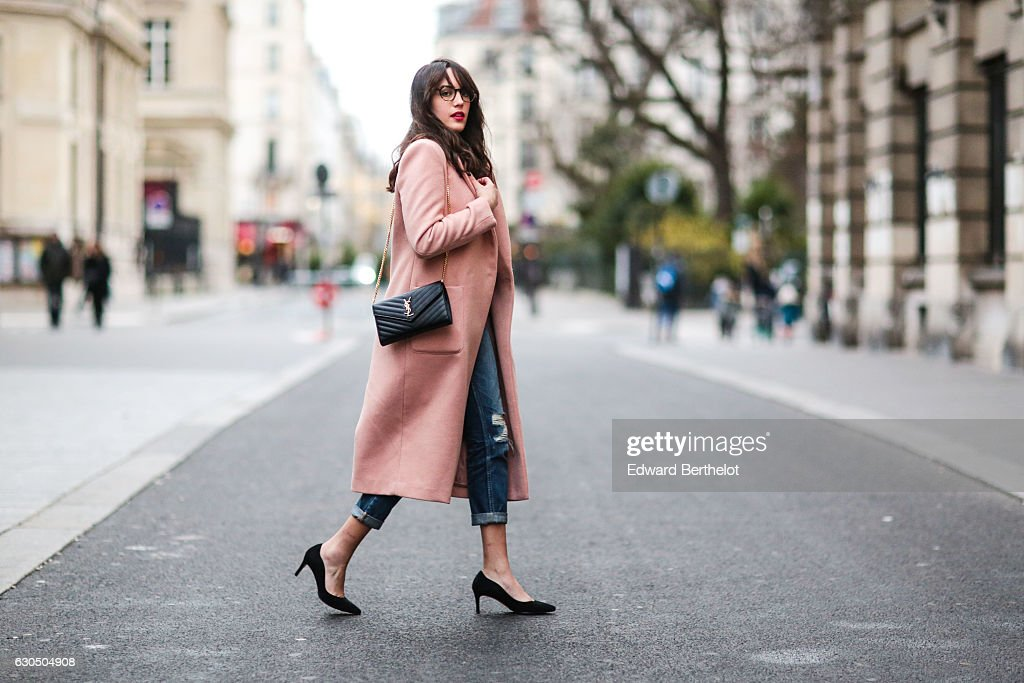 Sarah Benziane is wearing a New Look white top, Zara blue denim ripped jeans, Minelli black heels shoes, a New Look pink long coat, a Saint Laurent YSL bag, and L'Usine a Lunettes glasses, on December 24, 2016 in Paris, France.
