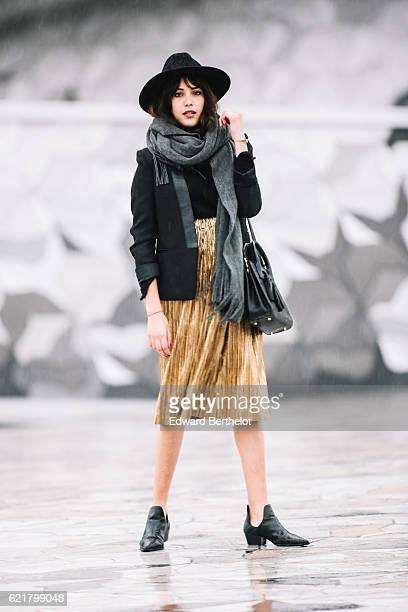 Sarah Benziane is wearing a Zara black top a Sandro black jacket a She Inside golden skirt Zara boots a black hat a black bag and a gray scarf on...