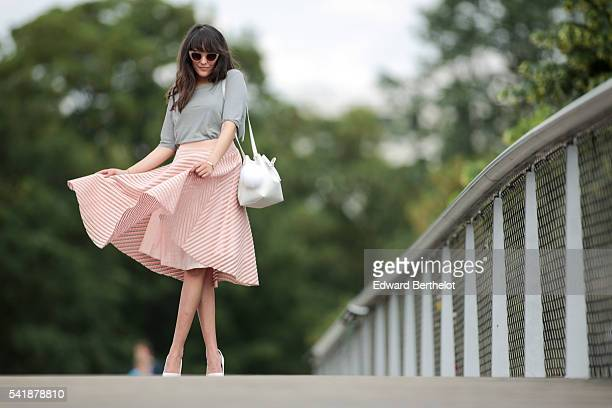 Sarah Benziane is wearing an American Apparel gray top a New Look pink skirt Bershka white heels shoes a Lancaster white bag and a Michael Kors...