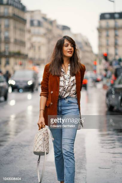 Sarah Benziane wears a brown suede New Look jacket blue jeans from Other Stories a Zara shirt with printed chains white shoes with brown heels from...