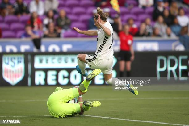 Sarah Bouhaddi of France makes a save against a leaping Svenja Huth of Germany during the SheBelieves Cup soccer match at Orlando City Stadium on...