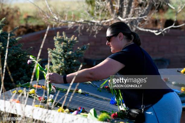 Sarah Boyd of Littleton Colorado places flowers at the Columbine Memorial at Clement Park in Littleton Colorado before a community vigil for the 20th...