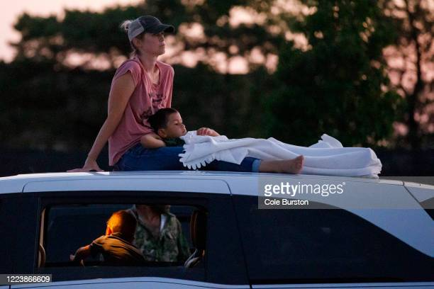 Sarah Boye and her son Miles sit atop their vehicle as they watch a drive-in Dean Brody concert to celebrate Canada Day on July 1, 2020 in Markham,...