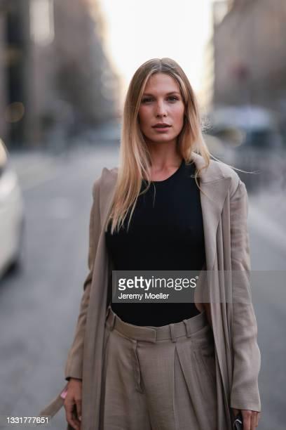 Sarah Brandner wearing a long blazer, wide leg pants and black top on July 29, 2021 in Berlin, Germany.