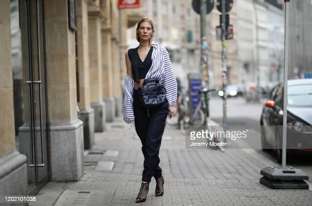 Sarah Brandner wearing Sportmax pants and blouse, VeeCollective bag, Jimmy Choo heels and Luilu earrings on January 26, 2020 in Berlin, Germany.