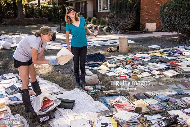 Sarah Brennecke and Claire Taylor dry out flooddamaged possessions in Taylor's front yard October 7 2015 in Columbia South Carolina The state of...