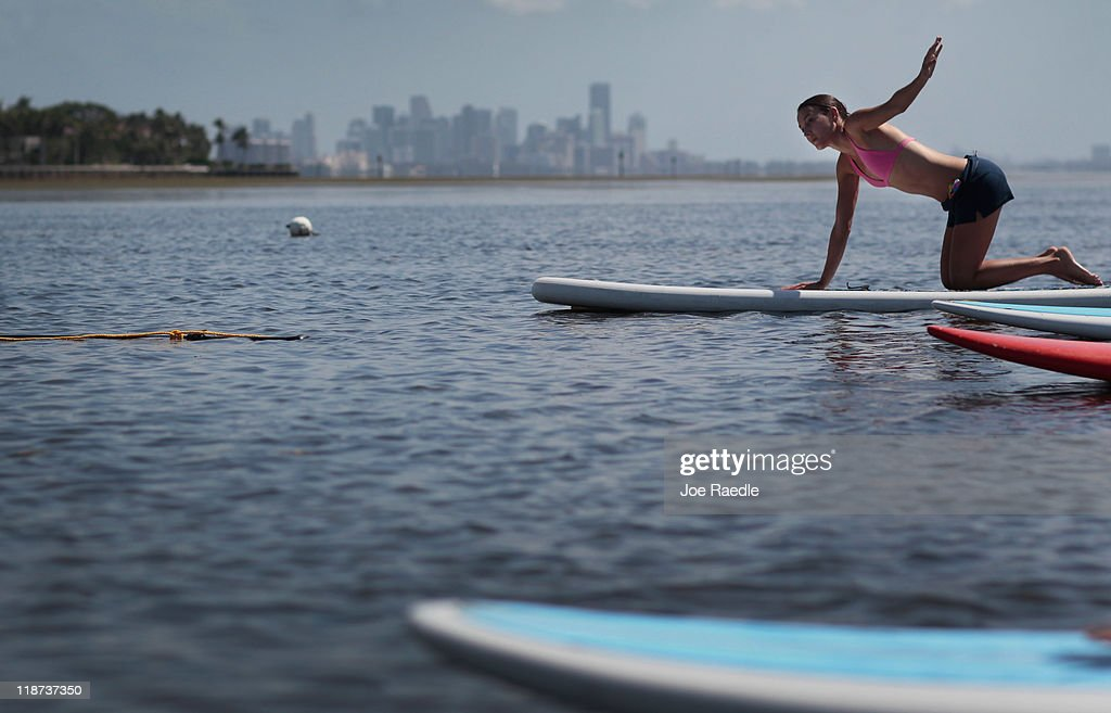 Sarah Castrellon enjoys a paddleboard yoga session at Adventure Sports Miami on July 10, 2011 in Miami, Florida. The paddle board is said to give the body's core more of a workout then in a gym since the platform is unstable and one must use the muscles to remain balanced on the board.