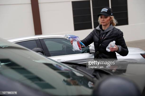Sarah Closson a volunteer with End of Watch Fund places bags of snacks and hand written notes for officers attending the funeral service for slain...