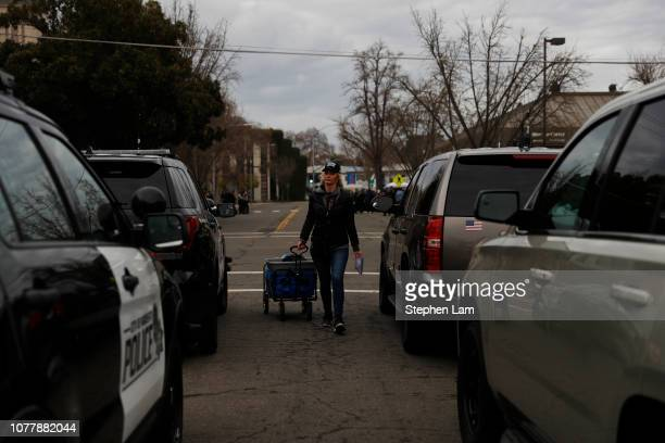Sarah Closson a volunteer with End of Watch Fund pulls a cart with snacks and notes for officers attending the funeral service for slain Newman...