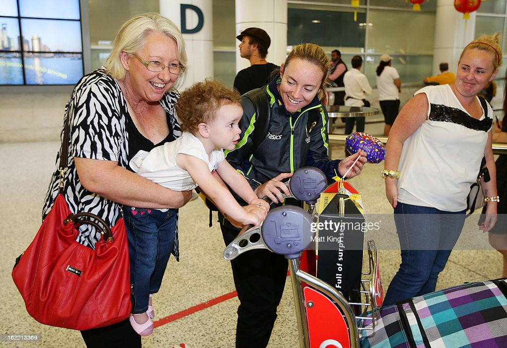 Sarah Coyte of the Australian women's cricket team shares a moment with her family after arriving home following their win in the 2013 World Cup at Sydney International Airport on February 21, 2013 in Sydney, Australia.
