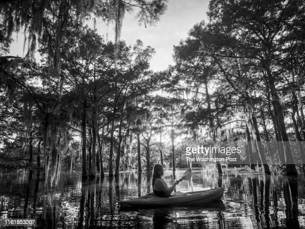 Sarah DeSimone paddles through Henderson Swamp in her kayak during sunset in the Atchafalaya Basin in Henderson La