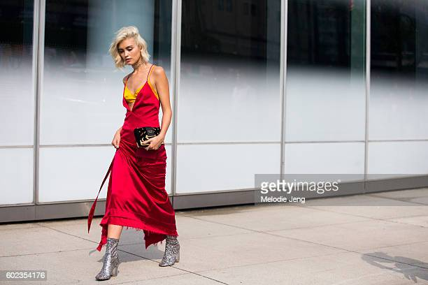 Sarah Ellen in a red slip dress yellow bra top Prada wallet and silver sparkly booties outside the Dion Lee show at Pier 59 on September 10 2016 in...