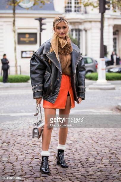 Sarah Ellen wearing a beige turtleneck sweater orange mini skirt black boots black oversize jacket and silver bag is seen after the Miu Miu show on...
