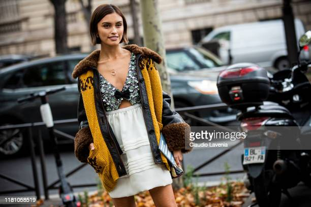 Sarah Ellen wearing a decorated white dress and brown leather jacket with yellow knitted details is seen outside the Miu Miu show during Paris...