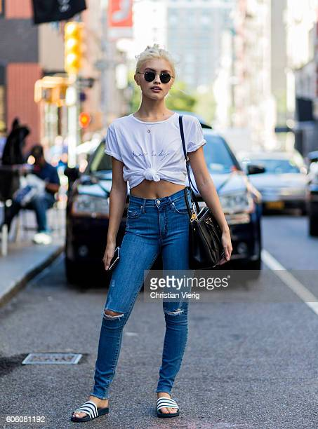Sarah Ellen wearing a white knotted tshirt ripped blue denim jeans and adilette on September 15 2016 in New York City