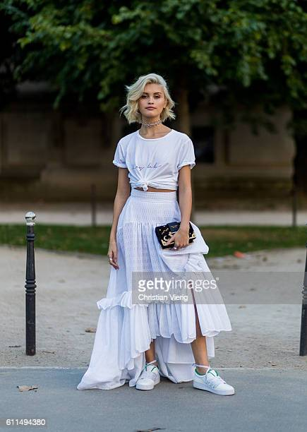 Sarah Ellen wearing a white skirt and tshirt and Prada bag and white sneakers outside of Barbara Bui on September 29 2016 in Paris France