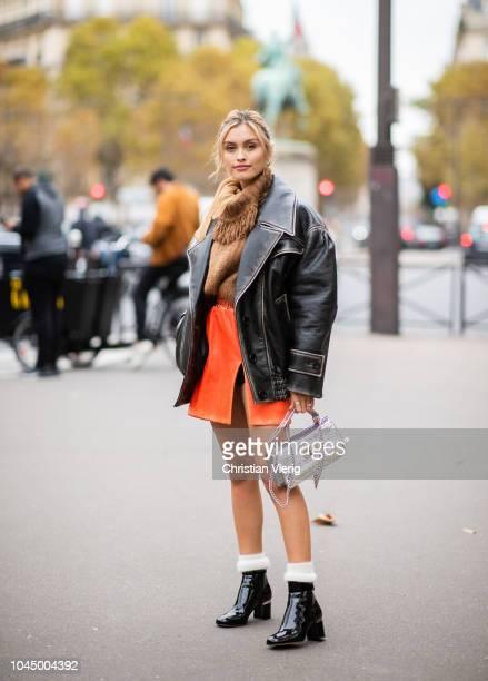 Sarah Ellen wearing oversized black leather jacket brown knit orange skirt with slit boots Miu Miu bag is seen outside Miu Miu during Paris Fashion...