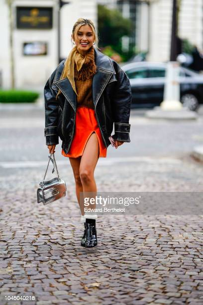 Sarah Ellen wears a black oversized leather jacket a brown wool pullover an orange skirt a silver bag outside Miu Miu during Paris Fashion Week...
