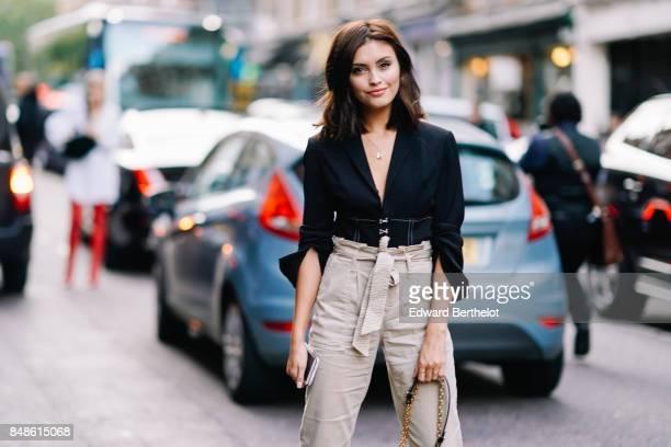 Sarah Ellen wears a black shirt gray pants black shoes a Vuitton bag outside Topshop during London Fashion Week September 2017 on September 17 2017...