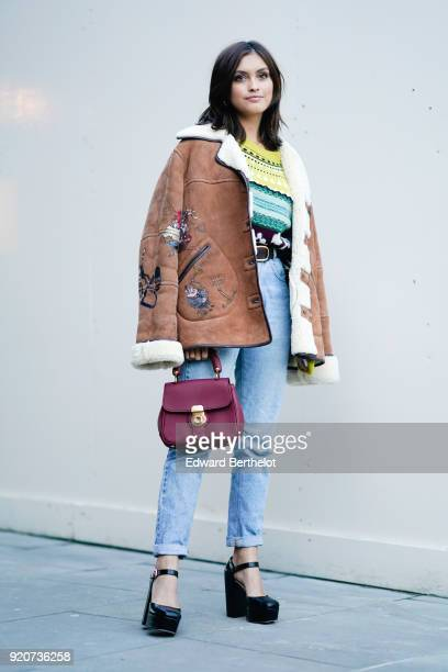 Sarah Ellen wears a brown aviator jacket a purple bag blue jeans black shoes during London Fashion Week February 2018 on February 17 2018 in London...