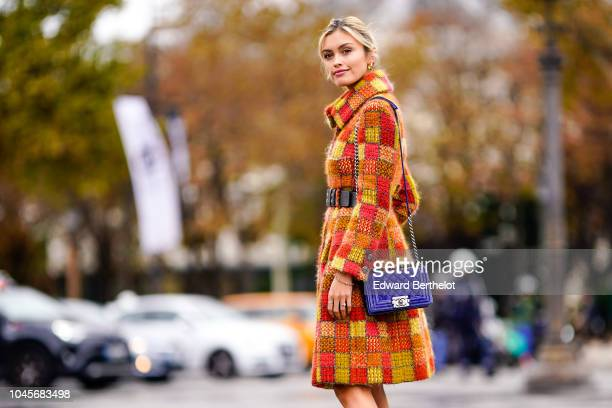 Sarah Ellen wears an orange and red checked tweed coat white boots a blue Chanel bag outside Chanel during Paris Fashion Week Womenswear...