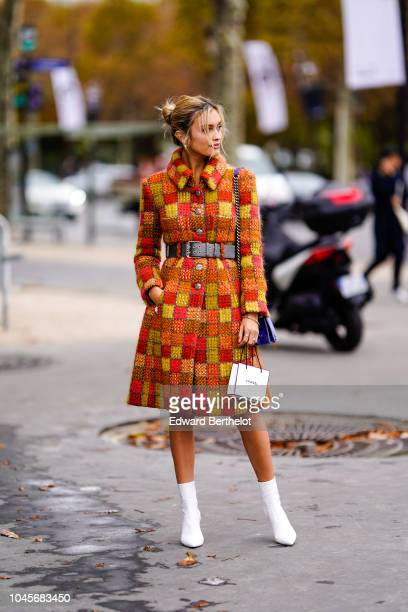 Sarah Ellen wears an orange and red checked tweed coat white boots outside Chanel during Paris Fashion Week Womenswear Spring/Summer 2019 on October...