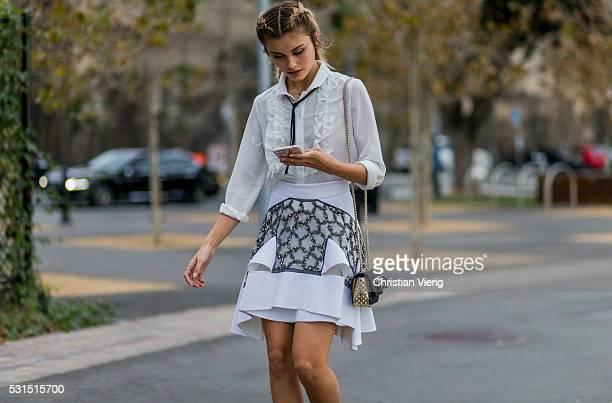 Sarah Ellen with braids wearing a white blouse and skirt from Toni Maticevski and a small Louboutin bag outside Toni Maticevski at MercedesBenz...