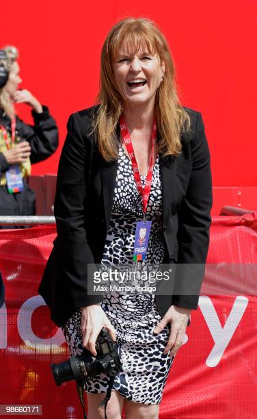 Sarah Ferguson The Duchess of York takes photographs of runners as she waits for daughter HRH Princess Beatrice of York to complete the Virgin London...