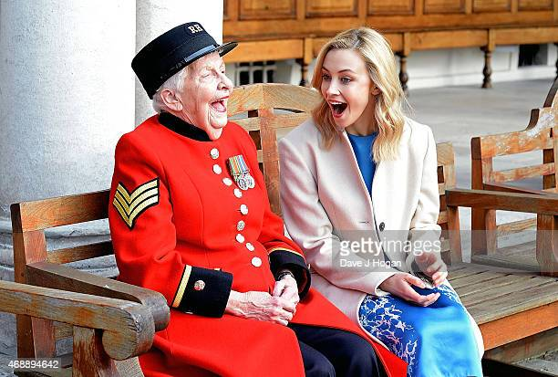 Sarah Gadon who plays Princess Elizabeth in 'A Royal Night Out' with Dorothy Hughes visits the Chelsea Pensioners to hear first hand their...