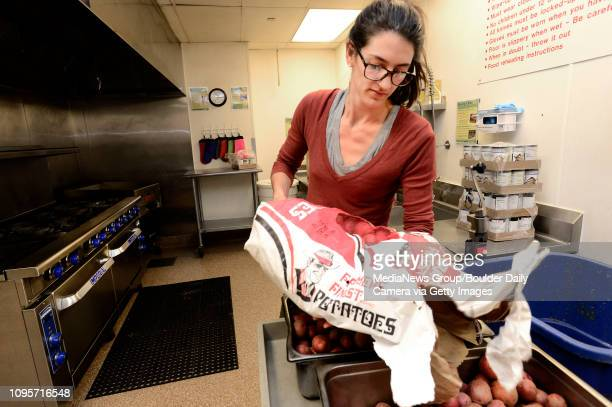 Sarah Haas Kitchen Manager for the Boulder Shelter empties a large bag of potatoes on Monday Sept 30 2013 The shelter which opens Tuesday was serving...