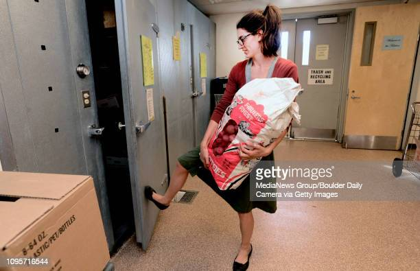 Sarah Haas Kitchen Manager for the Boulder Shelter for the Homeless uses her foot to close the refrigerator door as she carries a large bad of...