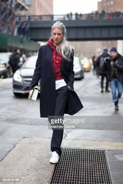 Sarah Harris is seen attending TIBI during New York Fashion Week wearing a navy coat with red hoodie on February 11 2017 in New York City