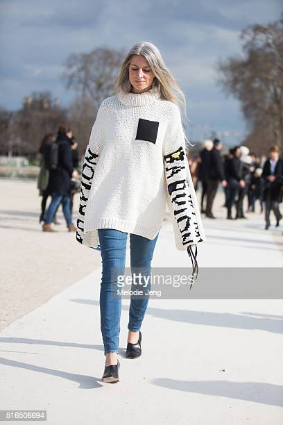 Sarah Harris of Vogue UK wears a white oversized knit turtleneck with 'Babylon' on the sleeves and ribbon attachments with skinny jeans at the...