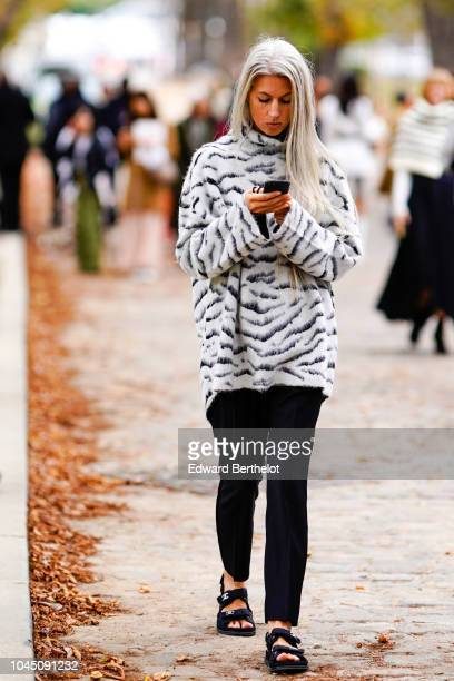 Sarah Harris wears a black and white zebra print pullover outside Beautiful People during Paris Fashion Week Womenswear Spring/Summer 2019 on October...