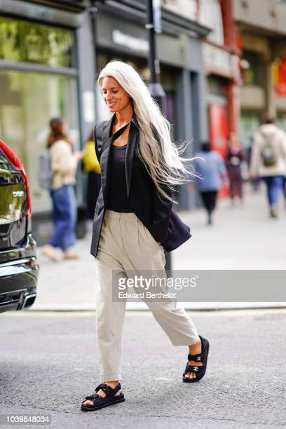 Sarah Harris wears a black blazer jacket wite pants black sandals a black top during London Fashion Week September 2018 on September 18 2018 in...