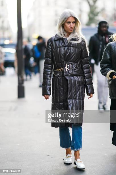 Sarah Harris wears a black long winter puffer coat blue ripped jeans white shoes outside Viktor Rolf during Paris Fashion Week Haute Couture...