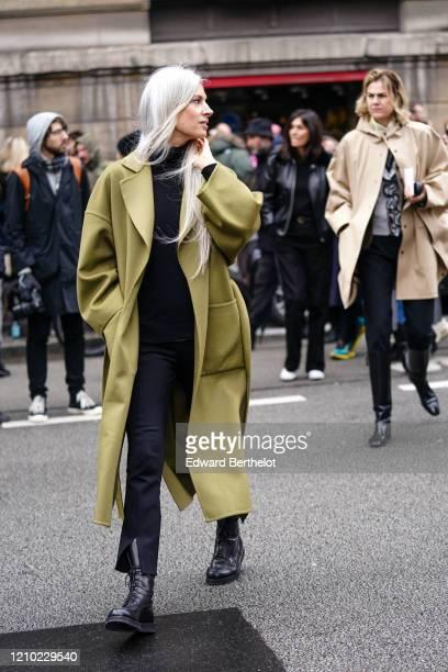 Sarah Harris wears a black turtleneck a mustardyellow oversized coat black laceup boots outside Akris during Paris Fashion Week Womenswear...