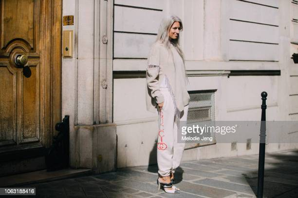Sarah Harris wears a tan jeweled sweater and white Gucci sweatpants outside the Altuzarra show during Paris Fashion Week Spring/Summer 2019 on...