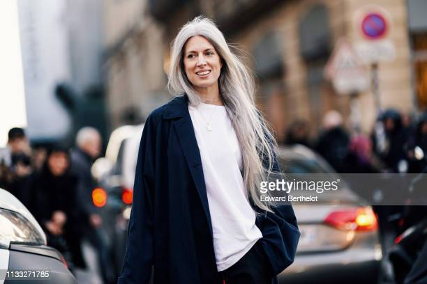 Sarah Harris wears a white tshirt a long dark jacket black pants white shoes outside CDG Comme des Garcons during Paris Fashion Week Womenswear...